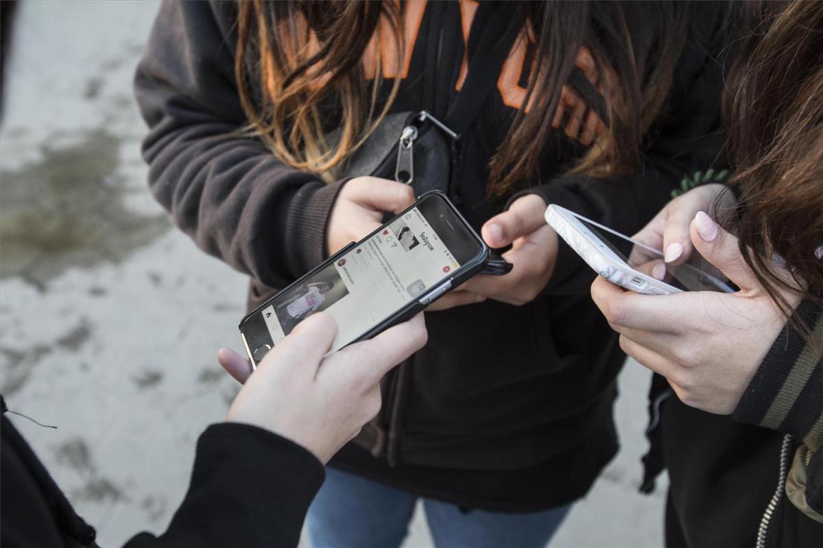 Händer fulla med mobiler