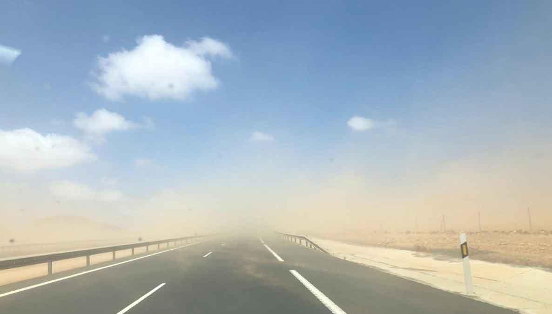 Sand blåser över vägen